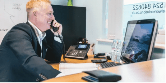 smiling recruitment consultant picking up phone in front of the computer